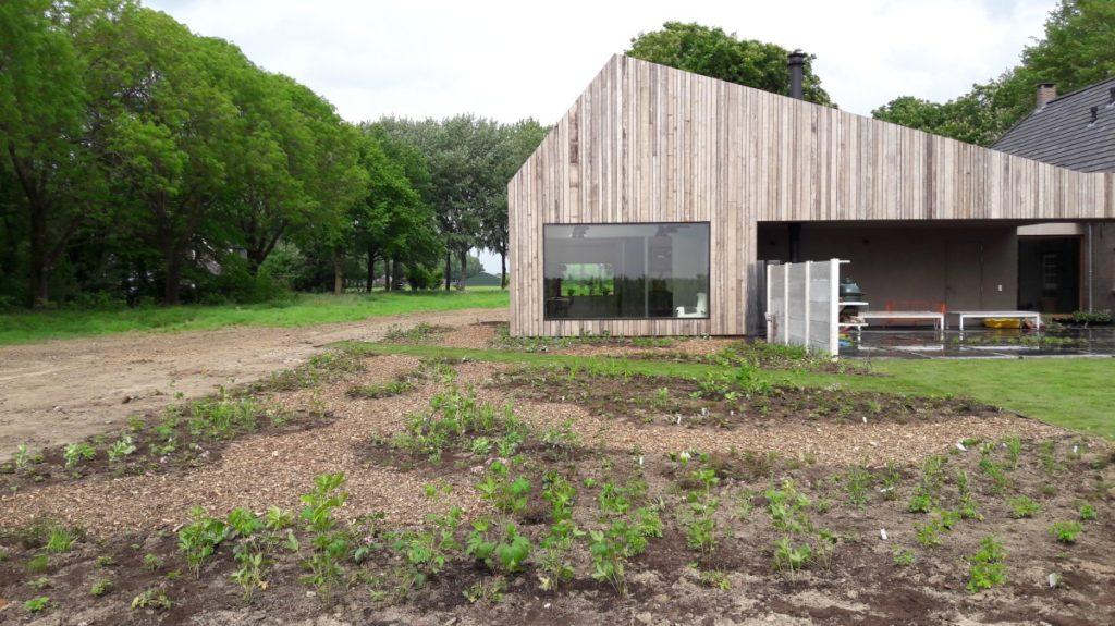 Een fraaie vaste planten tuin met paadjes van houtsnippers wat een prachtige overgang is naar het landelijk gebied om de woning